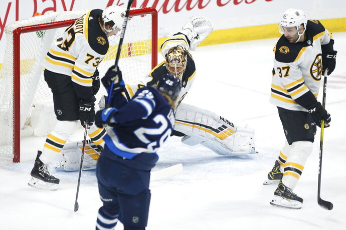 Winnipeg Jets' Patrik Laine (29) scores on Boston Bruins goaltender Tuukka Rask as Charlie McAvoy (73) and Patrice Bergeron (37) defend during the first period of an NHL hockey game Friday, Jan. 31, 2020, in Winnipeg, Manitoba. (John Woods/The Canadian Press via AP)