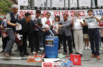 South Korean small and medium-sized business owners throw papers showing logos of major Japanese brands into a trash can during a rally calling for a boycott of Japanese products in front of the Japanese embassy in Seoul, South Korea, Monday, July 15, 2019. South Korea and Japan last Friday, July 12, failed to immediately resolve their dispute over Japanese export restrictions that could hurt South Korean technology companies, as Seoul called for an investigation by the United Nations or another international body. The signs read: