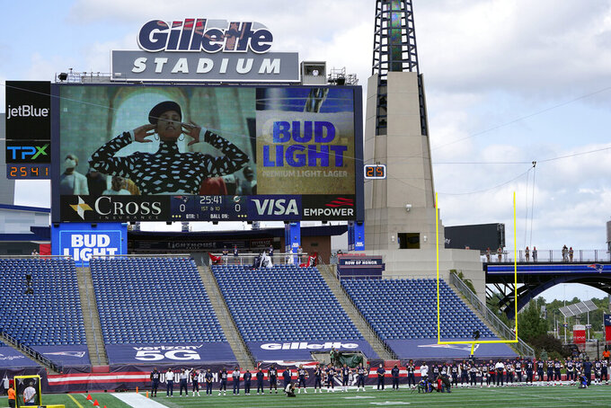 "New England Patriots stand during the singing of ""Lift Every Voice and Sing"" by Alicia Keys, on the video screen, before an NFL football game against the Miami Dolphins, Sunday, Sept. 13, 2020, in Foxborough, Mass. (AP Photo/Charles Krupa)"