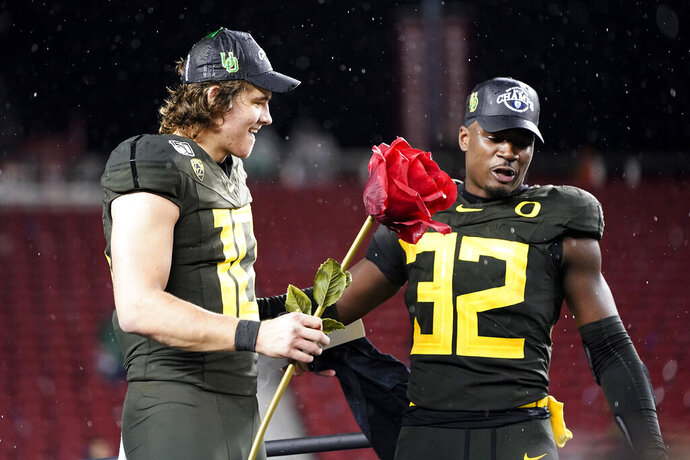 Oregon quarterback Justin Herbert (10) and teammate La'Mar Winston Jr. (32) celebrate after Oregon defeated Utah 37-15 in an NCAA college football game for the Pac-12 Conference championship in Santa Clara, Calif., Friday, Dec. 6, 2018. (AP Photo/Tony Avelar)