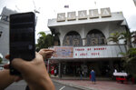 A woman takes a photo of a movie ticket outside the Scala theater Friday, July 3, 2020 in Bangkok, Thailand. The Scala theater has shut its doors after 51 years as a shrine for Thai movie-goers. (AP Photo/Sakchai Lalit)