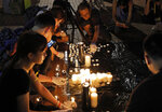 People light candles during a vigil to mourn the recent suicide of a woman due to the government's policy on the extradition bill, in Hong Kong Saturday, July 6, 2019. A vigil is being held in Hong Kong for a woman who fell to her death this week, one of three apparent suicides linked to ongoing protests over fears that freedoms are being eroded in this semi-autonomous Chinese territory. (AP Photo/Vincent Yu)