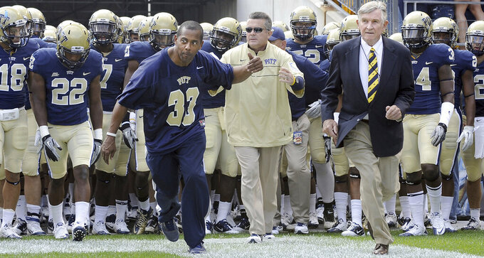 In this Sept. 24, 2011 photo, Tony Dorsett and Johnny Majors, right,  help Pitt head coach Todd Graham lead his team onto the field to take on Notre Dame during an during an NCAA college football game at Heinz Field in Pittsburgh.  Majors, the coach of Pittsburgh's 1976 national championship team and a former coach and star player at Tennessee, died Wednesday morning, June 3, 2020, at home in Knoxville, Tenn., according to a statement from his wife, Mary Lynn Majors. He was 85.  (Matt Freed/Pittsburgh Post-Gazette via AP)