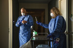 In this photo provided by the Alfred-Wegener-Institut and taken on May 6, 2020, Nina Machner, right, holds a COVID-19 test swab as colleague Tim Heitland puts on gloves, before testing a MOSAiC scientist, in Bremerhaven, Germany. They prepared for icy cold and trained to watch for polar bears, but a pandemic just wasn't part of the program. Now dozens of scientists are sitting in quarantine, waiting for permission to sail forth and capture a crucial moment in the polar calendar that's essential to their year-long Arctic research mission. (Alfred-Wegener-Institut via AP)