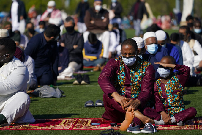 People participate in an Eid al-Fitr ceremony in Overpeck County Park in Ridgefield Park, N.J., Thursday, May 13, 2021. Millions of Muslims across the world are marking a muted and gloomy holiday of Eid al-Fitr, the end of the fasting month of Ramadan - a usually joyous three-day celebration that has been significantly toned down as coronavirus cases soar. (AP Photo/Seth Wenig)