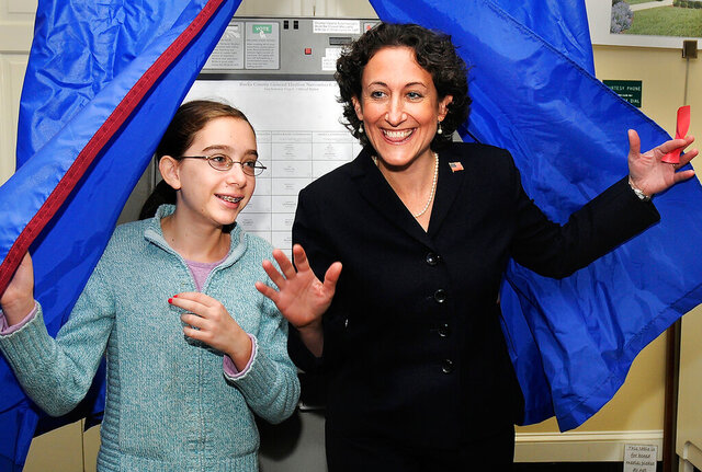 FILE - in this Nov. 6, 2012, file photo, Democratic congressional candidate Kathy Boockvar steps out of the voting booth with her daughter, Colette, after casting her vote on Election Day at the Pine Run Community in Doylestown, Pa. Boockvar, Pennsylvania's Secretary of State, said Wednesday, Sept. 30, 2020, it appears that the nine military ballots thrown out by an election office worker in Wilkes-Barre was a mistake and not