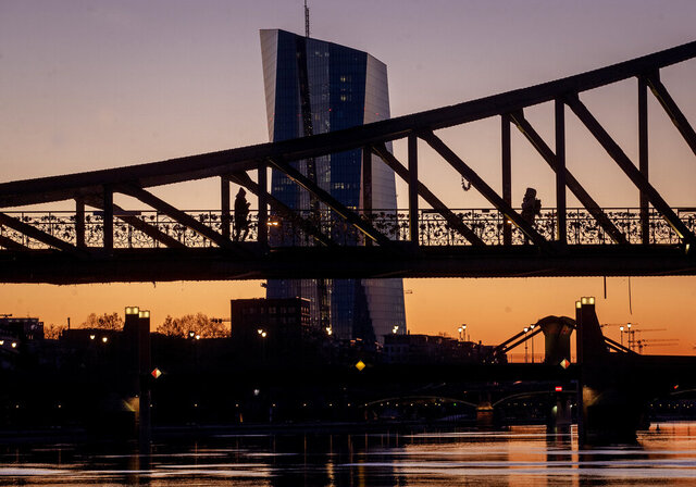 Two women walk over a bridge with the European Central Bank in background in Frankfurt, Germany, as the sun rises Monday, March 30, 2020. Due to the coronavirus the economy expects heavy losses. For most people, the new coronavirus causes only mild or moderate symptoms, such as fever and cough. For some, especially older adults and people with existing health problems, it can cause more severe illness, including pneumonia. (AP Photo/Michael Probst)
