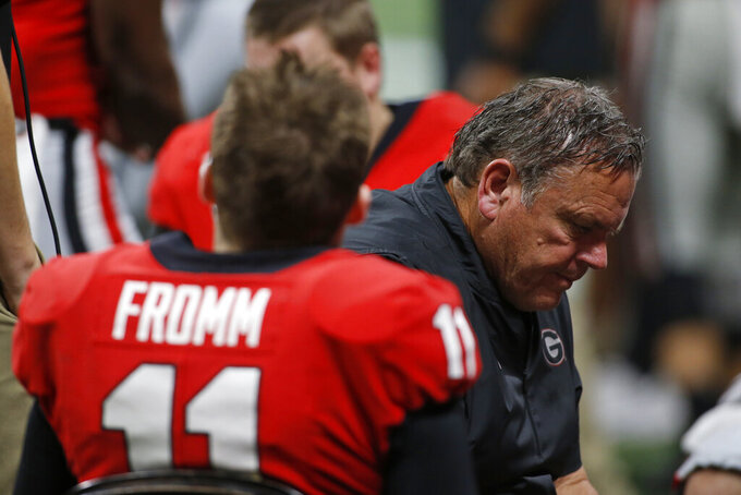 Georgia quarterback Jake Fromm (11) sits with offensive line coach Sam Pittman and the Georgia offensive lineman in the final moments of the team's NCAA college football game against LSU for the Southeastern Conference championship, Saturday, Dec. 7, 2019, in Atlanta. (Joshua L. Jones/Athens Banner-Herald via AP)
