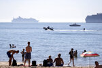 A person on a water skis off the the beach at Bournemouth, Southern England, Friday Aug. 7, 2020.  The UK could see record-breaking temperatures with forecasters predicting Friday could be the hottest day of the year. (Andrew Matthews/PA via AP)