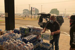 Jonathan Thompson of the Keizer, Oregon, Chamber of Commerce delivers donated bottled water on Tuesday, Sept. 8, 2020, to the Oregon State Fairgrounds in Salem, which is now an evacuation center as wildfires threaten towns in Oregon. High winds kicked up wildfires across the Pacific Northwest on Tuesday, burning hundreds of thousands of acres, mostly destroying the small town of Malden in eastern Washington state and forcing evacuations and highway closures in Oregon. (AP Photo/Andrew Selsky)