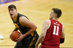 Iowa center Luka Garza drives to the basket past Wisconsin forward Micah Potter, right, during the first half of an NCAA college basketball game, Sunday, March 7, 2021, in Iowa City, Iowa. (AP Photo/Charlie Neibergall)