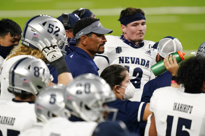 Nevada coach Jay Norvell speaks with players during the first half of an NCAA college football game against UNLV, Saturday, Oct. 31, 2020, in Las Vegas. (AP Photo/John Locher)