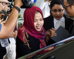 In this March 11, 2019, photo, Indonesian Siti Aisyah, center, smiles as she leaves Shah Alam High Court in Shah Alam, Malaysia. The Indonesian woman held two years on suspicion of killing North Korean leader's half brother Kim Jong Nam was freed from custody Monday after prosecutors unexpectedly dropped the murder charge against her. (AP Photo/Yam G-Jun)