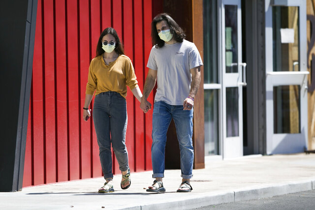 Hana Morris, left, and Forrest Golic wear masks as they walk hand in hand Monday, June 22, 2020, in Yakima, Wash. Washington state will require people to wear facial coverings in most indoor and outdoor public settings, under a statewide public health order announced Tuesday by Gov. Jay Inslee in response to ongoing COVID-related health concerns. Yakima County, which has been among the hardest hit by the outbreak, has even more stringent requirements under a separate proclamation issued by Inslee that also takes effect Friday. (Amanda Ray / Yakima Herald-Republic via AP)