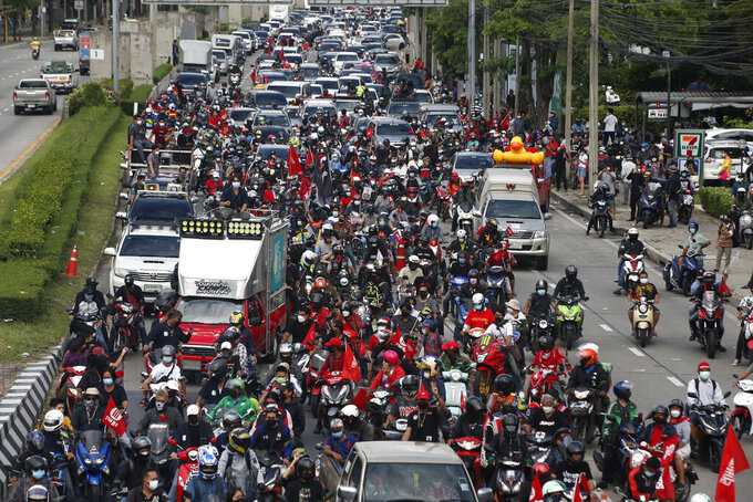 """Anti-government protesters block the road with cars and motorcycles as a part of their """"car mob"""" demonstrations along several roads in Bangkok, Thailand, Sunday, Aug. 29, 2021. A long line of cars, trucks and motorbikes wended its way Sunday through the Thai capital Bangkok in a mobile protest against the government of Prime Minister Prayuth Chan-ocha. The protesters on wheels hope their nonviolent action, dubbed a """"car mob,"""" can help force the ouster of Prayuth, whom they accuse of botching the campaign against the coronavirus. (AP Photo/Anuthep Cheysakron)"""