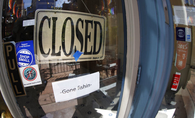 FILE - In this Thursday, June 18, 2020, file photo, a closed sign hangs in the door of The Market, a long-time restaurant and food store located in Larimer Square, that has closed because of the new coronavirus, in downtown Denver. State governments are pushing for help from Congress to fix budget gaps caused by the coronavirus pandemic and economic shutdowns. (AP Photo/David Zalubowski, File)