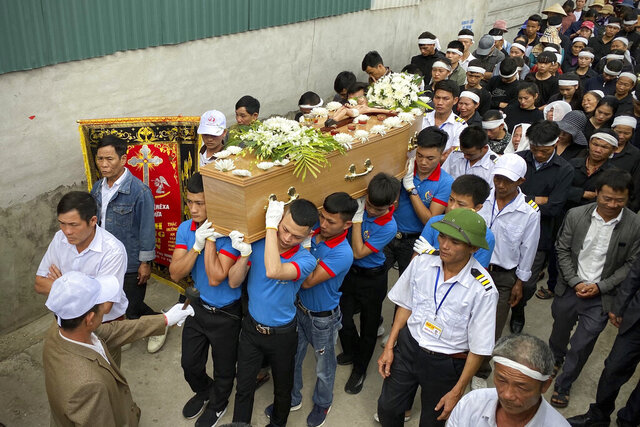 Relatives of Bui Thi Nhung walk behind her casket during a funeral procession to Phu Thang church ahead of Nhung's burial on Sunday, Dec. 1, 2019 in the village of Do Thanh, Vietnam. The body of 19-year old Nhung was among the last remains of the 39 Vietnamese who died while being smuggled in a truck to England last month that were repatriated to their home country on Saturday. (AP Photo/Hau Dinh)