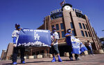 Los Angeles Dodgers fans Oliver Olson, left, of San Diego, Juan Campo and Rudy Soto, both of Los Angeles, hold up flags outside the main entrance to Coors Field as fans return for the first inning of a baseball game between the Dodgers and Colorado Rockies Thursday, April 1, 2021, in Denver. (AP Photo/David Zalubowski)