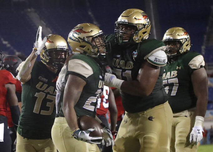 UAB running back Spencer Brown, center, is congratulated by wide receiver Collin Lisa (13) and offensive lineman Rishard Cook, right, after scoring a touchdown during the first half of the Boca Raton Bowl NCAA college football game against Northern Illinois, Tuesday, Dec. 18, 2018, in Boca Raton, Fla. (AP Photo/Lynne Sladky)