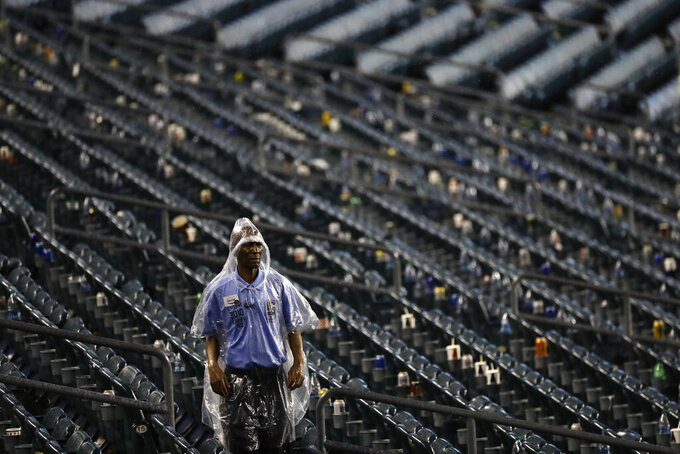 A worker walks through the stands as a storm ends a preseason NFL football game between the Philadelphia Eagles and the Baltimore Ravens, Thursday, Aug. 22, 2019, in Philadelphia. (AP Photo/Michael Perez)