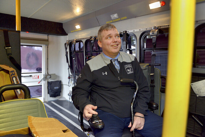 In this Dec. 10, 2019 photo, Lee, Mass. Police Chief Jeffrey Roosa, who has amyotrophic lateral sclerosis, also known as ALS, looks at the inside of a wheelchair van donated to him in Holyoke, Mass. The family of the late Judge William Boyle donated the van formerly used by Boyle, who died from the same disease. (Don Treeger/The Republican via AP)