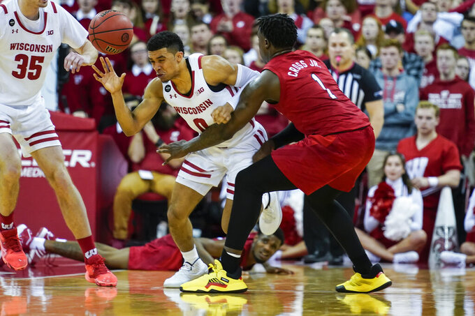 Wisconsin's D'Mitrik Trice (0) knocks the ball loose from Nebraska's Kevin Cross (1) during the second half of an NCAA college basketball game Tuesday, Jan. 21, 2020, in Madison, Wis. Wisconsin won 82-68. (AP Photo/Andy Manis)