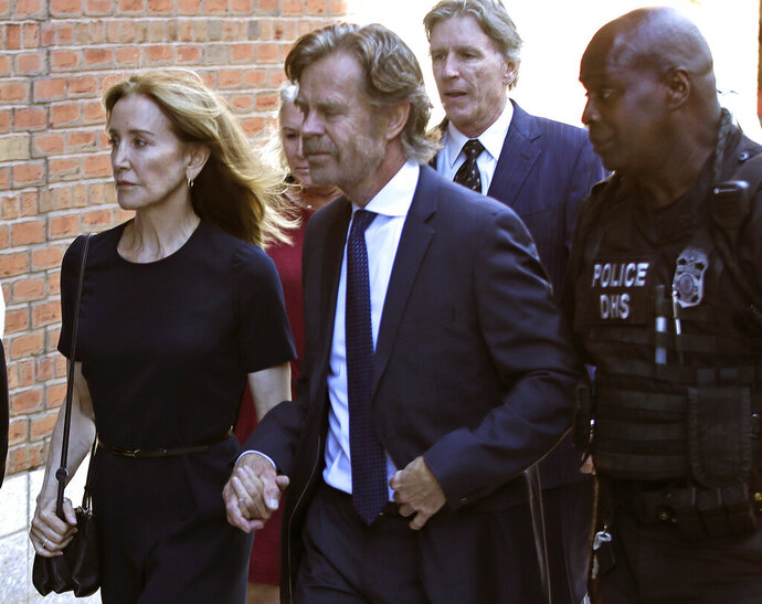 Felicity Huffman arrives at federal court with her husband William H. Macy and her brother Moore Huffman Jr., back, for sentencing in a nationwide college admissions bribery scandal, Friday, Sept. 13, 2019, in Boston.  (AP Photo/Elise Amendola)