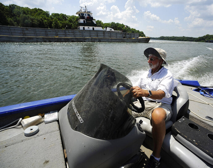 In this Tuesday, July 9, 2019 photo, Fred Hansard drives a boat past a tugboat and barge on the Tennessee-Tombigbee Waterway at Demopolis, Ala. Hansard, president of the Demopolis Yacht Basin, is frustrated with uneven development along the 234-mile waterway, which was supposed to be a catalyst for commerce that would transform a poor region when it opened in 1985. (AP Photo/Jay Reeves)