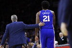 In this photo taken Jan. 6, 2020, Philadelphia 76ers head coach Brett Brown, left, walks Joel Embiid off the court after Embiid injured his finger during an NBA basketball game against the Oklahoma City Thunder in Philadelphia. Embiid injured the radial collateral ligament in the ring finger in the first half Monday night against Oklahoma City. (AP Photo/Matt Slocum)
