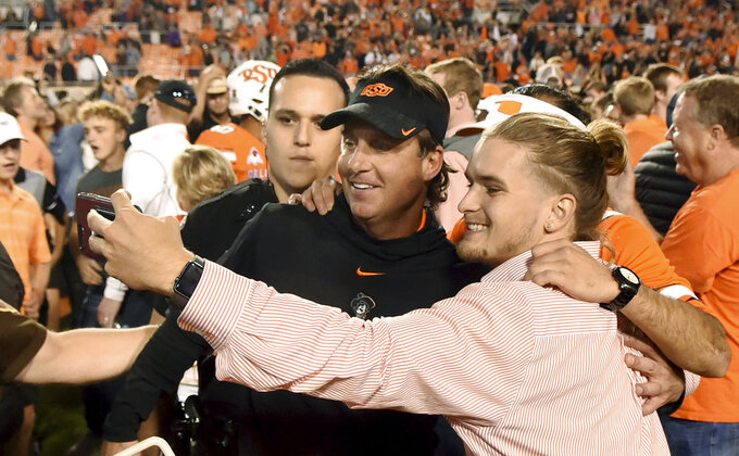 Oklahoma State head coach Mike Gundy takes a photo with fans following an NCAA college football game in Stillwater, Okla., Saturday, Oct. 27, 2018. Oklahoma State defeated Texas 38-35. (AP Photo/Brody Schmidt)