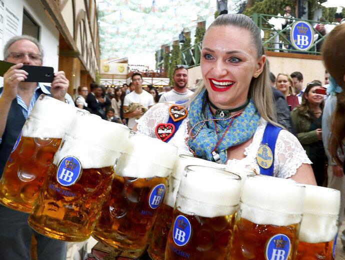 Une serveuse tient des verres de bière lors de l'ouverture du 186ème festival de la bière 'Oktoberfest' à Munich, en Allemagne, le samedi 21 septembre 2019. (AP Photo / Matthias Schrader)