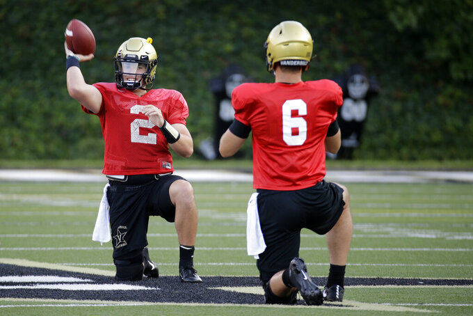 In this Aug. 5, 2019, photo, Vanderbilt quarterback Deuce Wallace (2) warms up with quarterback Riley Neal (6) during an NCAA college football practice in Nashville, Tenn. Vanderbilt has won at least five games each of the past three seasons and reached two bowls in that span. They've also won three straight against in-state rival Tennessee for their longest winning streak in this series since the 1920s. (AP Photo/Mark Humphrey)