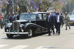 Bodyguards surround the car carrying Zimbabwe President Emmerson Mnangagwa at the opening session of parliament in Harare, Tuesday, Oct, 1, 2019. Zimbabwe's opposition lawmakers have walked out of Parliament as President Emmerson Mnangagwa presented his state of the nation address, a sign of the political tensions still gripping the country. (AP Photo/Tsvangirayi Mukwazhi)