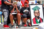FILE - Trinetta Brown, center left, 19, and Triniya Brown become emotional during a memorial service for their brother, Michael Brown, Thursday, Aug. 9, 2018, in the Canfield Green apartment complex in Ferguson, Mo. St. Louis County's top prosecutor announced Thursday, July 30, 2020, that he will not charge the former police officer who fatally shot Brown. But, he said,