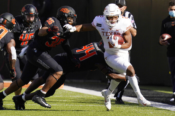 Texas running back Roschon Johnson (2) is pursued by Oklahoma State linebacker Kamryn Farrar (44) and linebacker Na'drian Dizadare (36) during the first half of an NCAA college football game in Stillwater, Okla., Saturday, Oct. 31, 2020. (AP Photo/Sue Ogrocki)