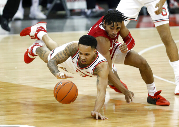 Ohio State guard CJ Walker, left, dives for a loose ball against Indiana guard Armaan Franklin during the first half of an NCAA college basketball game in Columbus, Ohio, Saturday, Feb. 13, 2021. (AP Photo/Paul Vernon)