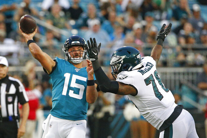 Jacksonville Jaguars quarterback Gardner Minshew (15) throws a pass as he is pressured by Philadelphia Eagles defensive end Shareef Miller during the first half of an NFL preseason football game, Thursday, Aug. 15, 2019, in Jacksonville, Fla. (AP Photo/Stephen B. Morton)