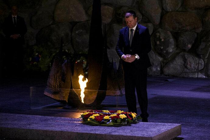 Lithuania's Prime Minister Saulius Skvernelis pays his respects at a ceremony at the Hall of Remembrance at the Yad Vashem Holocaust Memorial in Jerusalem, Tuesday Jan. 29, 2019. (AP Photo/Tsafrir Abayov)
