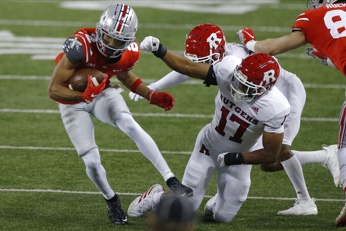 Ohio State receiver Chris Olave, left, escapes the grasp of Rutgers defenders Tre Avery, center, and Deion Jennings during the first half of an NCAA college football game Saturday, Nov. 7, 2020, in Columbus, Ohio. (AP Photo/Jay LaPrete)