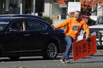 Anti-tax activist Tim Eyman darts across traffic after he stopped to shake hands with a motorist who honked at him as he waved a sign supporting Initiative 976, which would cut most car registration tabs to $30 in Washington state, Tuesday, Nov. 5, 2019, on election day in Bellevue, Wash. If passed by voters, the measure would leave state and local governments scrambling to pay for road paving and other transportation projects. (AP Photo/Ted S. Warren)