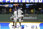 Milwaukee Brewers' Kolten Wong and Luis Urias celebrate after a baseball game against the Chicago Cubs Saturday, Sept. 18, 2021, in Milwaukee. The Brewers won 6-4 and clinched a spot in the 2021 Postseason. (AP Photo/Morry Gash)