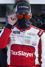 Myatt Snider looks over his sunglasses as he waits to start a NASCAR Xfinity Series auto race, Saturday, Feb. 27, 2021, in Homestead, Fla. Snider won the race at Homestead-Miami Speedway after Noah Gragson slammed into a lapped car with two laps remaining. (AP Photo/Wilfredo Lee)