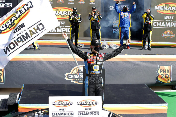 Jesse Love, center, waves a season champion banner as he celebrates on the championship stage following an ARCA Series auto race at Phoenix Raceway, Saturday, Nov. 7, 2020, in Avondale, Ariz. (AP Photo/Ralph Freso)