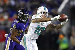 FILE - In this Oct. 26, 2017, file photo, Miami Dolphins wide receiver Kenny Stills (10) catches a pass in front of Baltimore Ravens cornerback Brandon Carr in the second half of an NFL football game in Baltimore. The Houston Texans continued a busy day of trades by addressing a glaring need to upgrade their offensive line by acquiring left tackle Laremy Tunsil from the Dolphins in a deal which also netted them receiver Kenny Stills, a source familiar with the deal tells The Associated Press.  (AP Photo/Nick Wass, File)