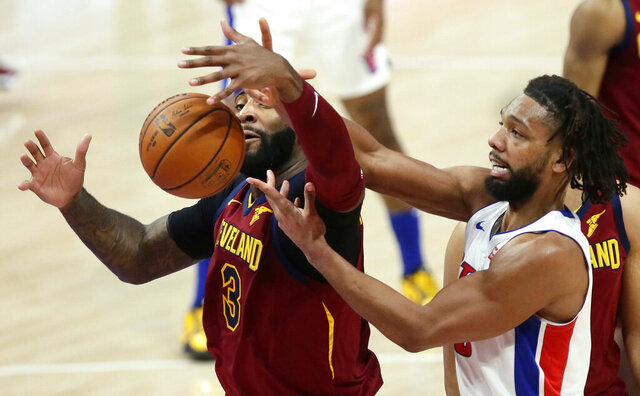 Cleveland Cavaliers center Andre Drummond, left,  blocks out Detroit Pistons center Jahlil Okafor, right, to grab a rebound during the first half of an NBA basketball game Saturday, Dec. 26, 2020, in Detroit. (AP Photo/Duane Burleson)