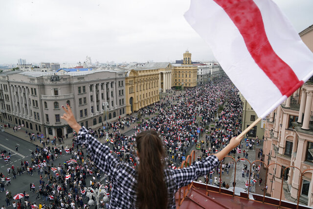 """FILE - In this Sunday, Aug. 3, 2020 file photo, a woman waves an old Belarusian national flag standing on the roof as Belarusian opposition supporters march to Independence Square in Minsk, Belarus. The Belarus government has cracked down hard on the news media, deporting some foreign journalists reporting in the country and revoking the accreditation of many Belarusian journalists. Two Moscow-based Associated Press journalists covering the recent protests in Belarus were deported to Russia on Saturday, Aug. 29, 2020. In addition, the AP's Belarusian staff were told by the government that their press credentials had been revoked. The AP said it decries the moves as a """"blatant attack on press freedom."""" Protests in Belarus began after the Aug. 9 election that officials said gave President Alexander Lukashenko a sixth term. Protesters say the election results were rigged and are demanding that Lukashenko resign after 26 years in power. (AP Photo/Evgeniy Maloletk"""