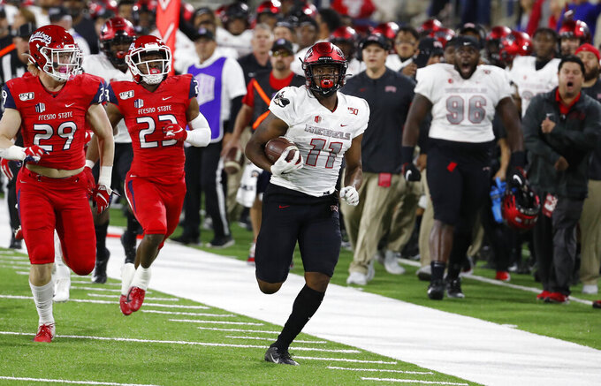 UNLV tight end Noah Bean for a long gain as Fresno State linebacker Justin Rice, left, and defensive back Juju Hughes pursue during the first half of an NCAA college football game in Fresno, Calif., Friday, Oct. 18, 2019. (AP Photo/Gary Kazanjian)