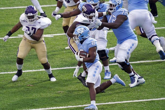 North Carolina running back Michael Carter (8) runs the ball while Western Carolina linebacker Ty Harris (37) looks to tackle during the first half of an NCAA college football game in Chapel Hill, N.C., Saturday, Dec. 5, 2020. (AP Photo/Gerry Broome)