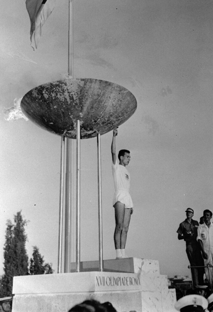 Italian student Giancarlo Peris holds the torch after lighting the Olympic flame in the tall tripod brazier on the perimeter of the Olympic Stadium in Rome, Aug. 25, 1960, at the formal opening of the XVII modern Olympiad. (AP Photo)