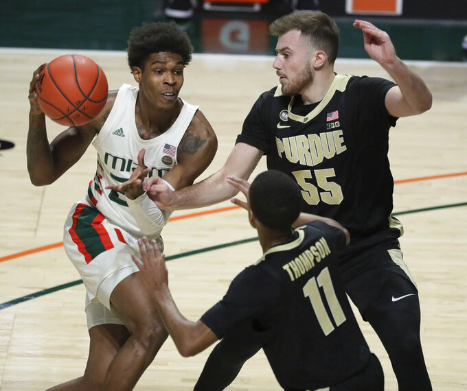Miami guard Kameron McGusty (23) looks to pass the ball around Purdue guards Sasha Stefanovic (55) and Isaiah Thompson (11) during the first half of an NCAA college basketball game Tuesday, Dec. 8, 2020, in Coral Gables, Fla. (Al Diaz/Miami Herald via AP)